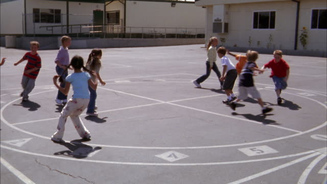 Wide shot children playing game of freeze tag on playground