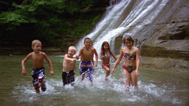 Wide shot children wading through stream at foot of waterfalls toward CAM/ Stony Brook State Park, New York