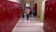 Wide shot children walking in primary school corridor/ girl putting backpack in locker and walking away/ Goram, Maine