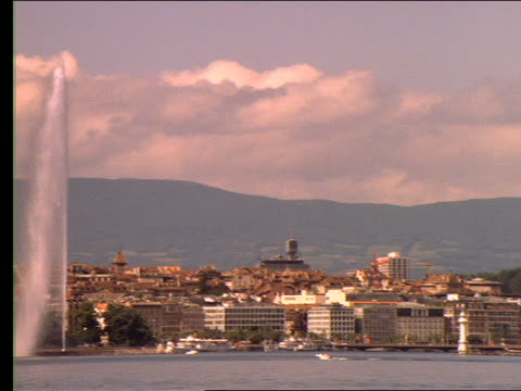wide shot PAN of  city on lake with mountains in background / Geneva