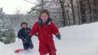 Wide shot - close-up Girl and boy pulling sled and running in snow / Franconia, Grafton County, New Hampshire, USA