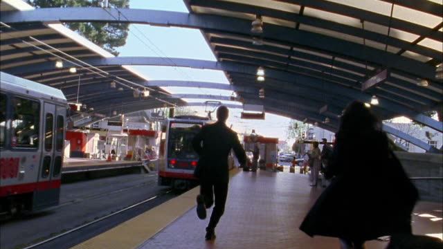 Wide shot commuters running to catch departing train
