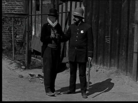 1918 B/W Wide shot cop chasing blindfolded man/ man pushing cop's hat over has eyes