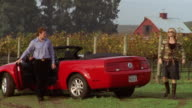 Wide shot couple arriving at vineyard in red convertible/ Napa Valley, California