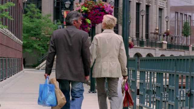 Wide shot couple holding hands, talking and carrying shopping bags on RiverWalk / Milwaukee, Wisconsin