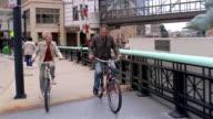 Wide shot couple riding bikes aross Wisconsin Avenue Bridge / passing Gertie the Duck statue / Milwaukee