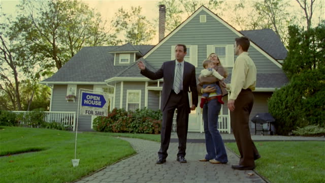 Wide shot couple with baby shaking real estate broker's hand and hugging as if buying house/ Solebury, Pennsylvania