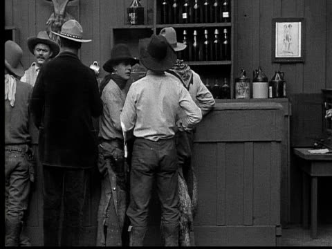 1915 B/W Wide shot Cowboys talking, smoking, and fighting in saloon