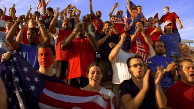 wide shot crane shot football fans standing + clapping in outdoor bleachers during game, holding American flags