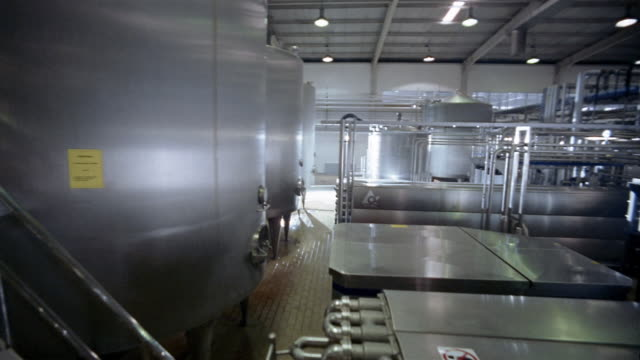 Wide shot crane shot staircase alongside large vats to machinery with extensive piping at dairy processing plant