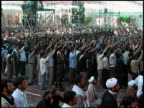 2003 wide shot crowd of men protesting with fists in air / Iran
