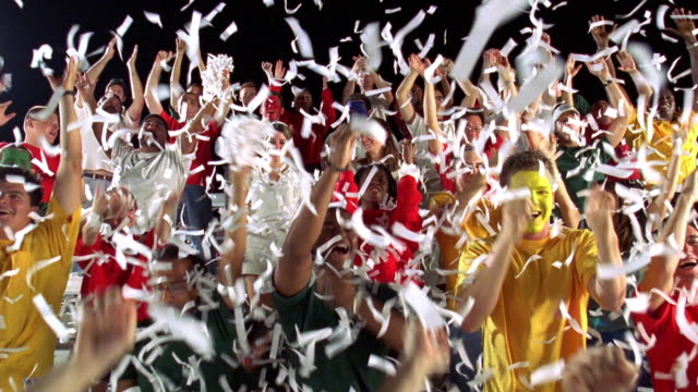 wide shot crowd of sports fans standing, cheering + throwing confetti in bleachers during game