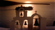 Wide shot cruise ship sailing past bell tower of chapel on Aegean Sea at sunset / Santorini, Greece