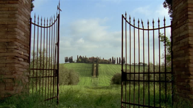 Wide shot cypress-tree lined path leading to hilltop house seen through gate / Tuscany, Italy