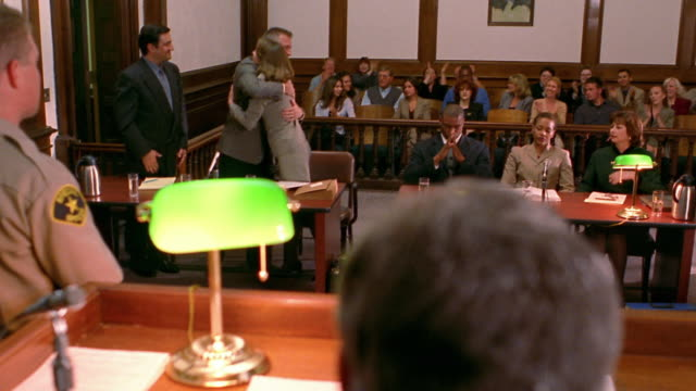 Wide shot defendant and his lawyers receiving positive verdict / reacting / back of judge's head in foreground