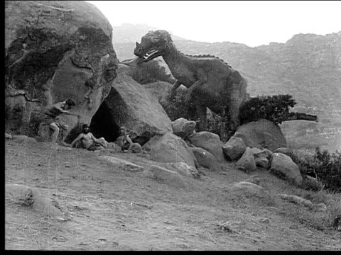 1914 B/W Wide shot Dinosaur eating outside cave entrance and frightening cavemen