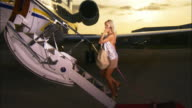 Wide shot Diva entering private airplane, talking on cell phone, and leading chihuahua up steps / Long Beach, California, USA