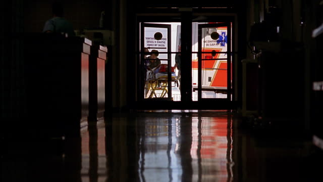 Wide shot doctors and paramedics in silhouette rushing patient on gurney down hall of hospital