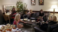 Wide shot dolly shot glam band sitting on couch in hotel / pan groupie sitting on floor and band playing instruments