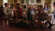 Wide shot dolly shot multi-generational family sitting at dining room table eating dinner