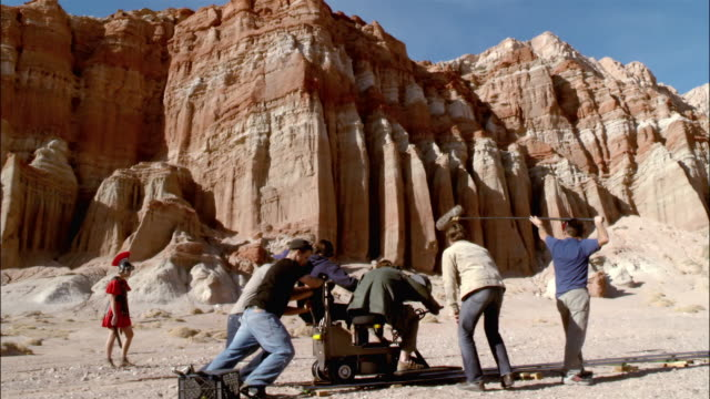 Wide shot dolly shot of film crew capturing dolly shot of actor dressed as Roman soldier running across desert landscape / Red Rock Canyon State Park, California