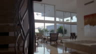 Wide shot dolly shot past bannister to living room w/ floor to ceiling windows