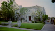 Wide shot dolly shot past five large houses in upscale neighborhood