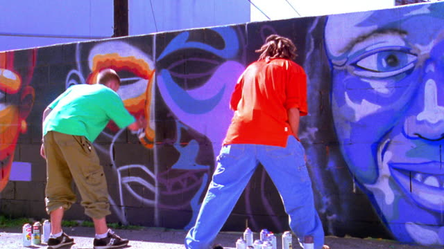 wide shot dolly shot REAR VIEW two young men spraypainting murals of faces (self portraits) on wall / Los Angeles