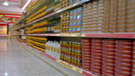 Wide shot dolly shot shopping cart point of view passing canned goods on shelves in aisle of grocery store