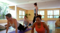 Wide shot dolly shot students in yoga class performing cobra and downward dog poses with instructor helping them