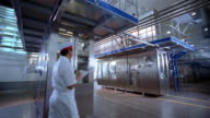 Wide shot dolly shot technician inspecting aseptic packaging chamber at milk processing plant / Bandung, Indonesia