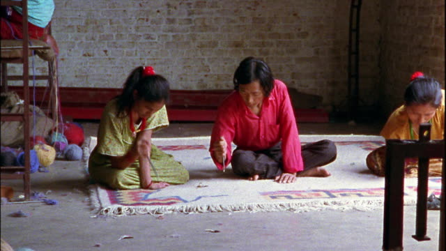 Wide shot dolly shot workers decorating and  weaving rugs at rug factory / Nepal