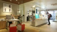 Wide shot employees and customers inside a Bouygues Telecom store operated by Bouygues SA in Paris France on Thursday July 3 An employee speaks with...