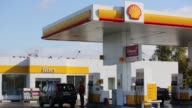 Wide shot employees work on the forecourt of a Shell gas station operated by Royal Dutch Shell Plc in Moscow Russia on Tuesday Sept 30 The Shell logo...