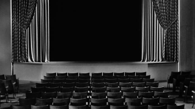 B/W wide shot empty theater with seats + stage/screen