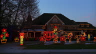 Wide shot exterior of house decorated with Christmas lights with animated display in front yard