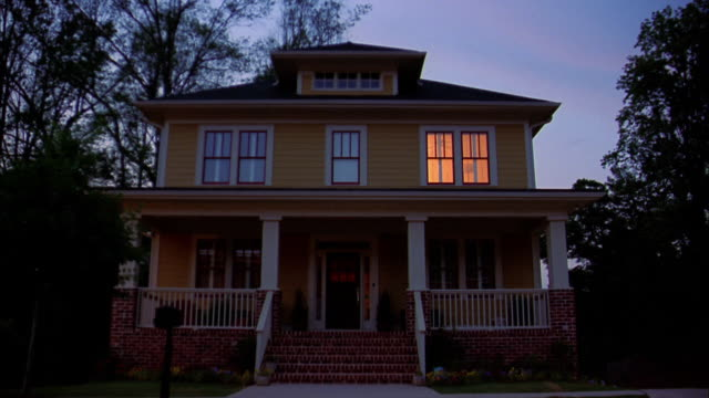 Wide shot exterior of house with lights in windows turning off