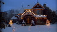 Wide shot exterior of snow-covered house decorated with Christmas lights
