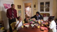 Wide shot family eating breakfast at dining room table / mother pouring milk into bowl of cereal