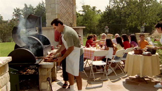 Wide shot family members attending barbecue in backyard / man smiling and presenting plate of meat to CAM