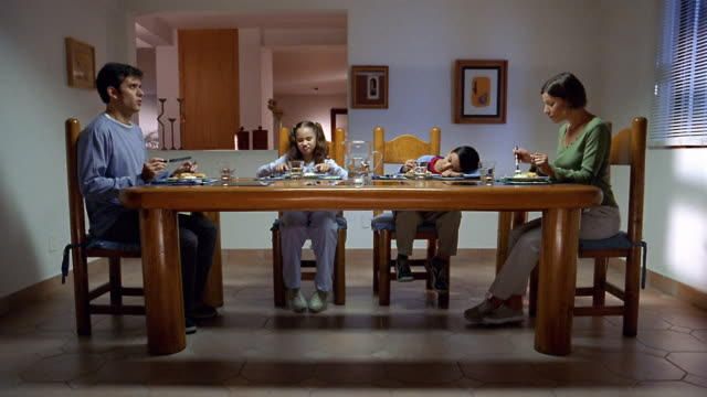 Wide shot family quietly eating meal in dining room / Mexico City