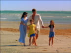 Wide shot family walking on beach holding hands / Miami, Florida