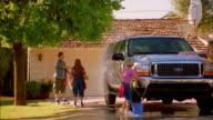 Wide shot family washing SUV in driveway / Phoenix, Arizona