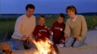 Wide shot family w/twin boys kneeling and roasting marshmallows on sticks by bonfire on beach