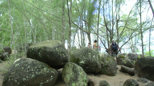Wide Shot Father and Sons Hike Through Boulders