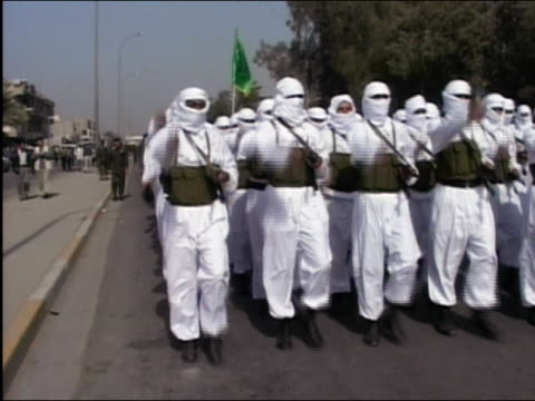 2003 wide shot Fedayeen Saddam men in white unifor marching and chanting in Baghdad Iraq / AUDIO