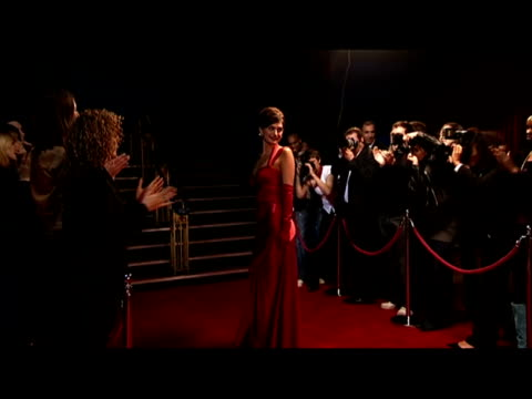 Wide shot female celebrity on red carpet as paparazzi takes photos/ zoom in celebrity woman/ London, England