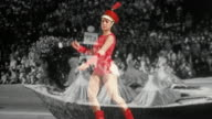 Wide shot female majorette in red uniform marching in place against VS black and white parade footage
