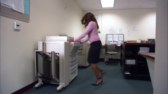 Wide shot female office worker kicking photocopier / Los Angeles