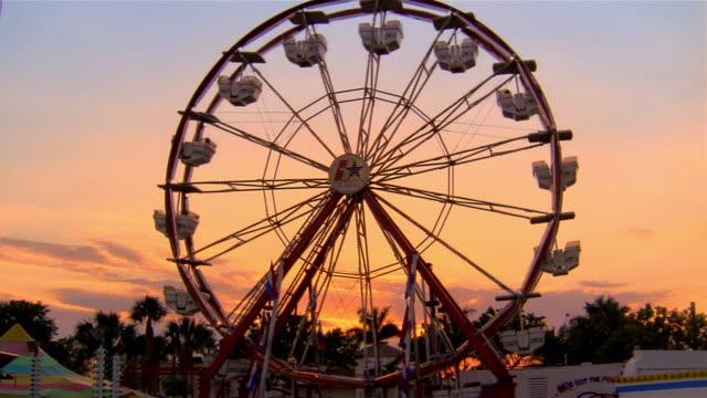 Wide shot ferris wheel at sunset